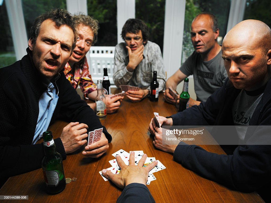 Men at table with drinks playing cards, portrait : Stock Photo