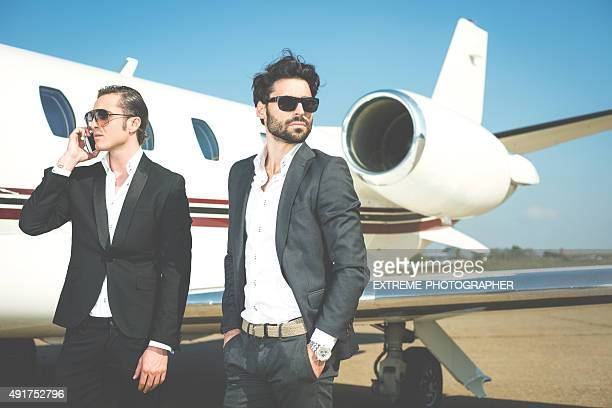 men at the airport track next to private jet airplane - hands in pockets stock pictures, royalty-free photos & images