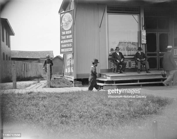 Men at the Mose Bone Sample Room Black River Falls Wisconsin 1900 Two men are sitting on chairs on the porch in front A male dwarf is walking on the...