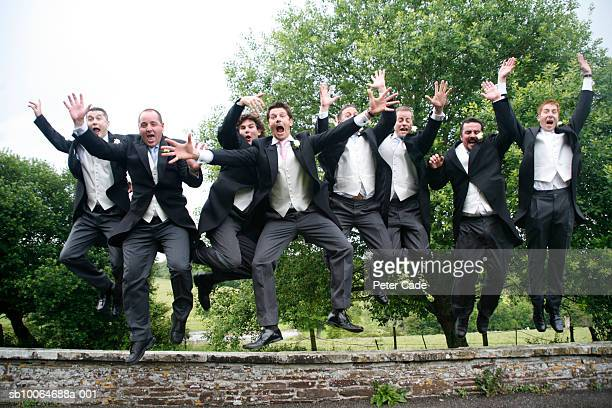 Men at wedding jumping off wall