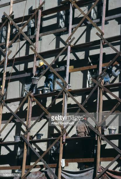 Men at work on a scaffolding to redo a building facade New York City US 1989