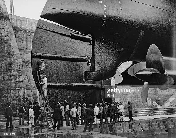 Men at work on the giant rudder of the Cunard superliner Mauretania in the dry dock at Cherbourg