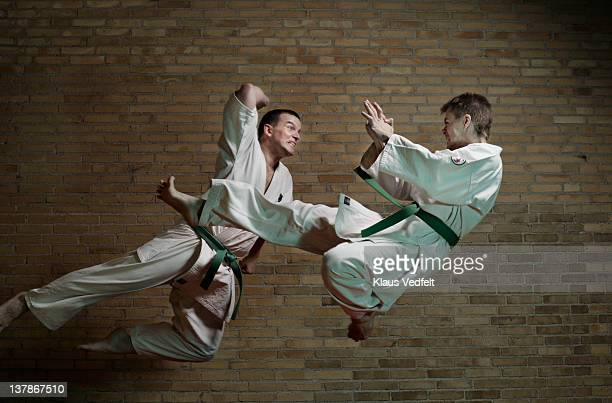 2 men attacking eachother in the air with karate