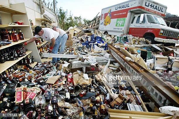 Men attempt to salvage bottles of liquor from a destroyed liquor store August 15, 2004 in Port Charlotte, Florida. Hurricane Charley destroyed many...