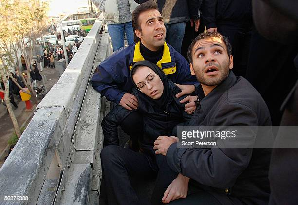 Men attend to a woman who fainted on a bridge overpass as Iranians mourn the death of 116 journalists and military men in a C130 plane crash with a...