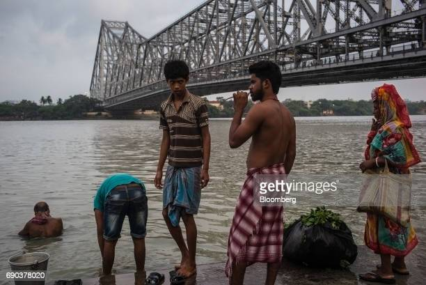 Men bathe on the banks of the Hooghly river near the Howrah Bridge in Kolkata India on Friday May 26 2017 India is scheduled to release firstquarter...