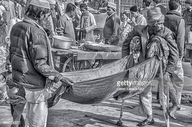 Men begging, one with leg deformed holding up a blanket draped for money to be tossed into it. Musllim men leaving afternoon prayer @ Jama Masjid...