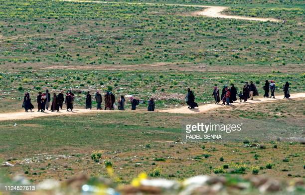 Men believed to be Islamic State fighters and their families walk in a field as they leave the IS' embattled holdout of Baghouz on February 13, 2019...
