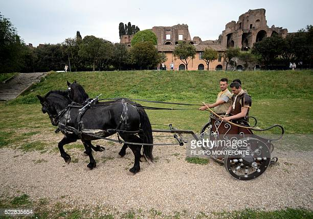Men belonging to historical groups and dressed as ancient roman centurions ride a Biga two horse chariot on the anniversary of the legendary...