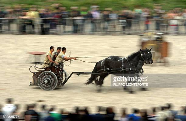 Men belonging to historical groups and dressed as ancient roman centurions ride a Biga two horse chariot against four gladiators on the anniversary...