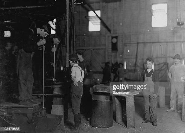 Men blow through the blowpipe while young mold boys watch ready to assist West Virginia 1908