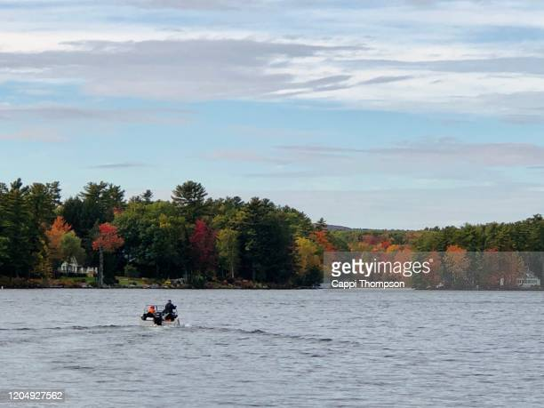 men boating in belgrade lake, maine usa during autumn - cappi thompson stock pictures, royalty-free photos & images