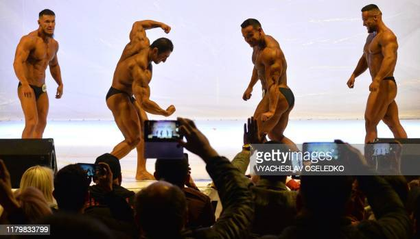Men bodybuilders attend the 'Bikini fitness' bodybuilding contest as people take pictures in Bishkek on November 3 2019