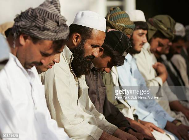 Men bow their heads during a Friday prayer service at the Blue Mosque in Kabul Afghanistan