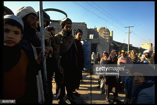 Men boys assembled on street in city under control of Taliban faction led by radical Islamic clerics winning civil war