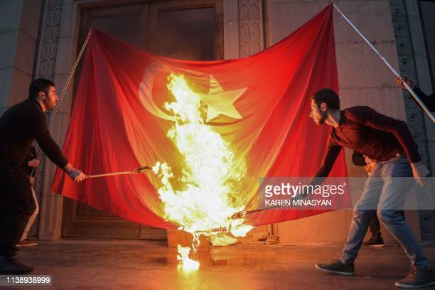 TOPSHOT Men burn a Turkish flag ahead of a torchlight procession as they mark the anniversary of the killing of 15 million Armenians by Ottoman...