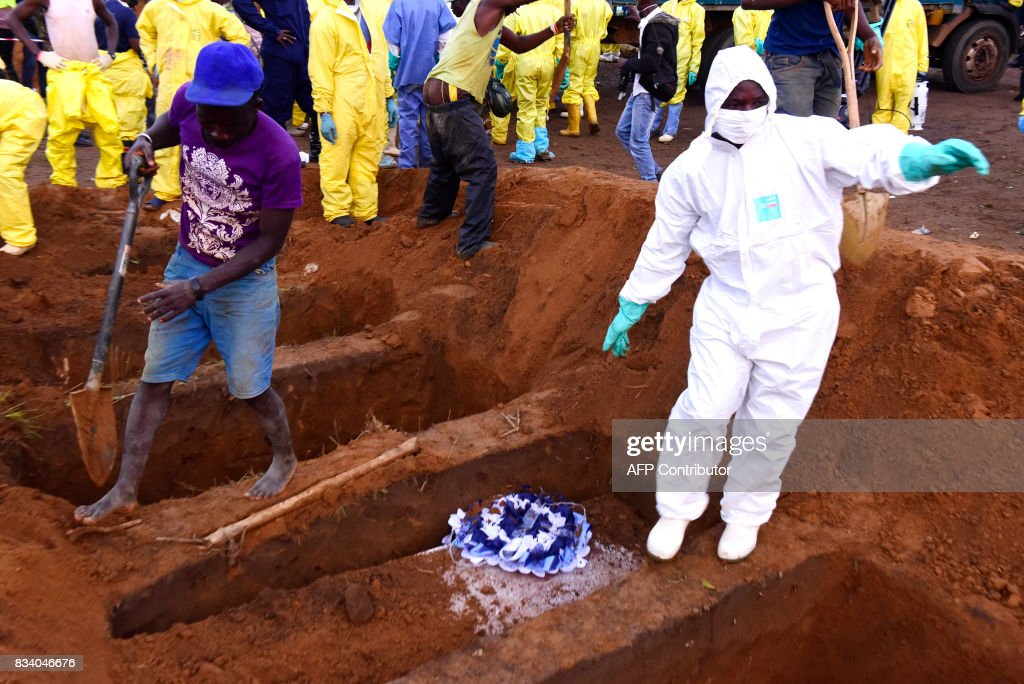 Men bury coffins of mudslide victims on August 17, 2017 at Waterloo cemetery near Freetown, Sierra Leone. Sierra Leone buried at least 300 victims of devastating floods on Thursday, as fears grew of more mudslides and accusations of government 'inaction' over deforestation and poor urban planning mounted. With the aim of clearing the overflowing central morgue, burials began around 1800 GMT in Waterloo, a nearby town where many victims of the Ebola crisis that hit the nation in 2014 were also laid to rest, according to a morgue official and an AFP journalist at the scene. PHOTO / SEYLLOU