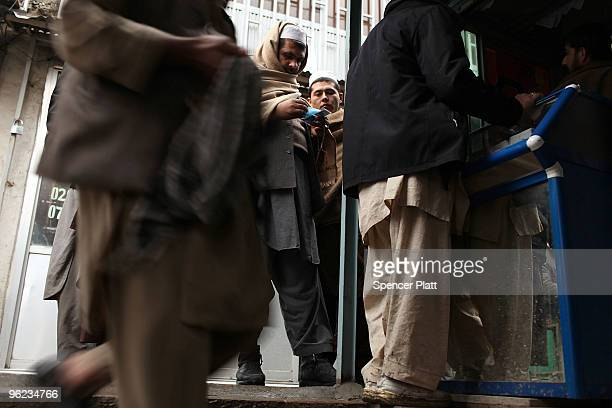 Men buy and trade currencies at a money market on January 28 2010 in Kabul Afghanistan London is hosting a critical daylong international conference...