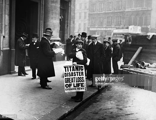 Men buy newspapers from a newsboy on a city street carrying the headline 'Titanic Disaster Great Loss of Life'