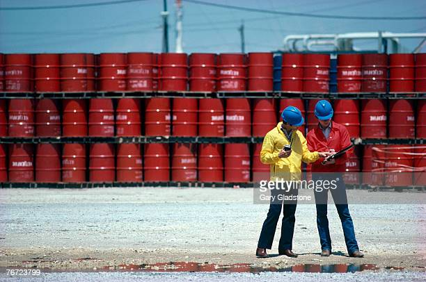 men by oil barrels - drum container stock photos and pictures