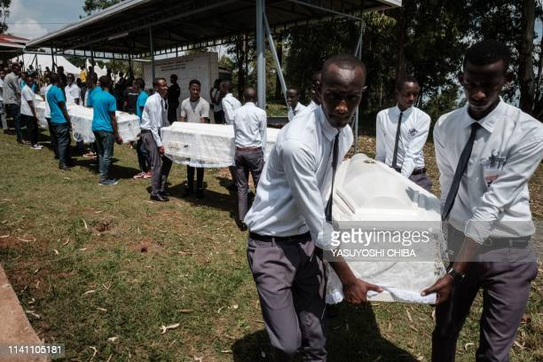 Men carry 81 coffins containing newly discoverd remains of 84,437 victims of the 1994 genocide during a funeral ceremony at the Nyanza Genocide...