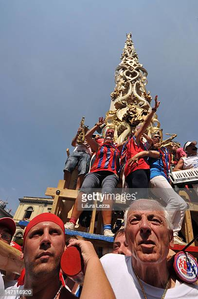 Men carry a 25metre tall 'giglio' wood and papiermache statue before it is displayed in the central square during the annual Festa dei Gigli 'The...