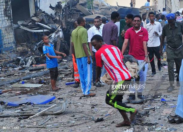 Men carry a body after two car bombs exploded in Mogadishu on October 28 2017 A car packed with explosives blew up outside a hotel in Mogadishu on...