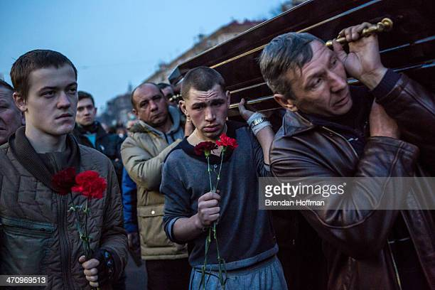 Men carry a casket containing the body of an antigovernment protester killed in clashes with police from Independence Square on February 21 2014 in...
