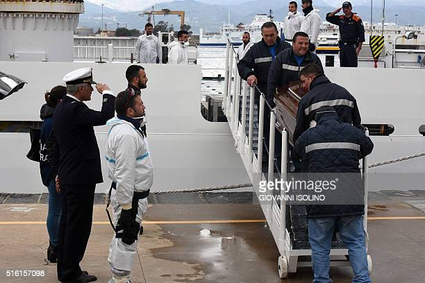 Men carry a coffin during the arrival of migrants and refugees in the port of Messina following a rescue operation at sea by the Italian Coast Guard...