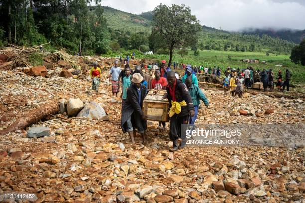 TOPSHOT Men carry a coffin on along a makeshift path on the river in Ngangu township Chimanimani Manicaland Province eastern Zimbabwe after the area...