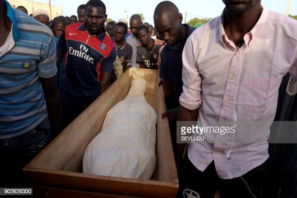 Men carry a coffin to cemetery on January 7 2018 in the regional capital Ziguinchor southern Senegal following an attack by armed men in the Bayotte...