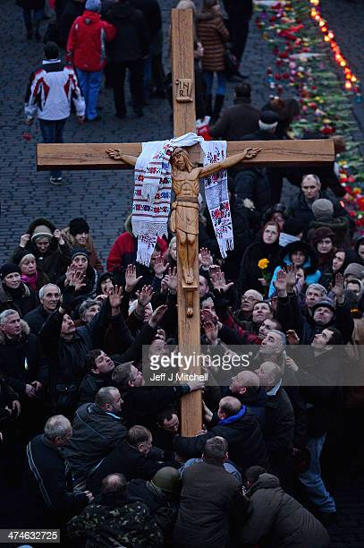 Men carry a cross of the crucifixion to points in Independence Square where antigovernment demonstrators were killed in clashes with police last week...