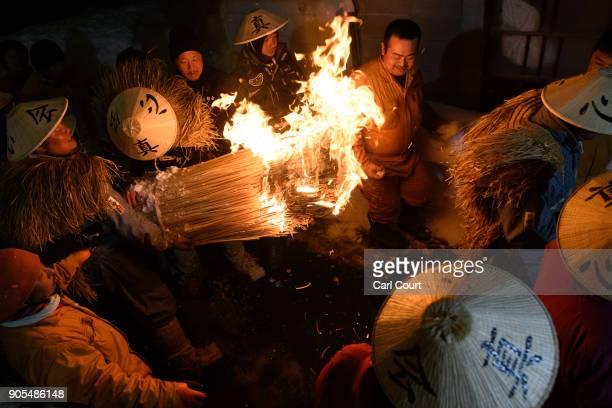 Men carry a flaming bundle of sticks towards the shrine as they begin the Nozawaonsen Dosojin Fire Festival on January 15 2018 in Nozawaonsen Japan...