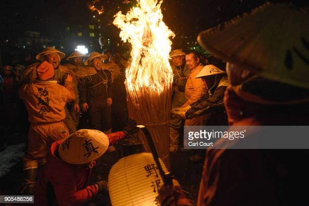Men carry a flaming bundle of sticks towards the shrine as they begin the Nozawaonsen Dosojin Fire Festival on January 15 2018 in Nozawaonsen Japan...