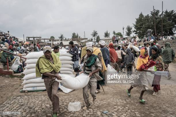 Men carry a sack of wheat during a food distribution by the World Food Programme for internally displaced people in Debark, 90 kilometres of the city...