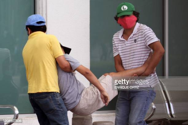 TOPSHOT Men carry a sick man into a hospital in Guayaquil Ecuador on April 1 2020 Residents of Guayaquil in Ecuador's southwest express outrage over...