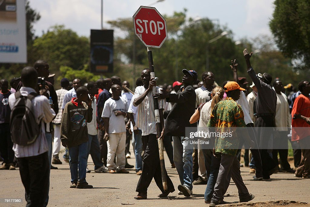 Men carry a stop sign after riots began during a mass funeral for the victims of clashes on January 23, 2008 in Nairobi, Kenya. More than 600 people have died in post-election violence after allegations election manipulation by the incumbent president sparked riots in the African nation.