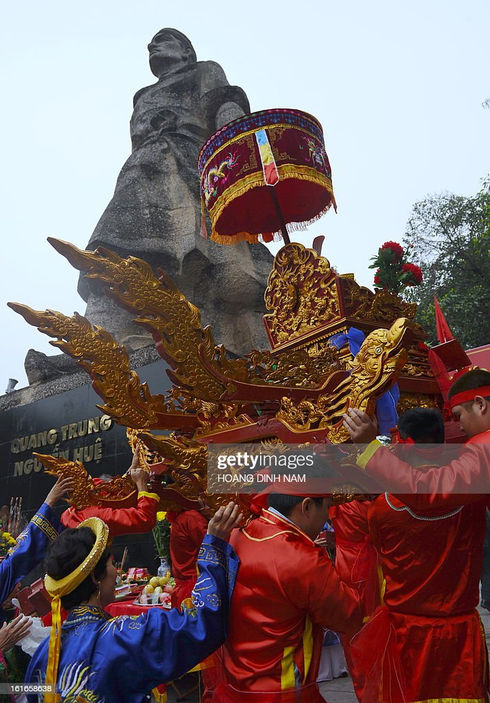 Men carry an altar in front of the statue of King Quang Trung during a ceremony to mark the 224th anniversary of Vietnam's Dong Da victory over Chinese invading troops in the spring of 1789 at the site of the historical battlefield in Hanoi on February 14, 2013. AFP PHOTO/HOANG DINH Nam