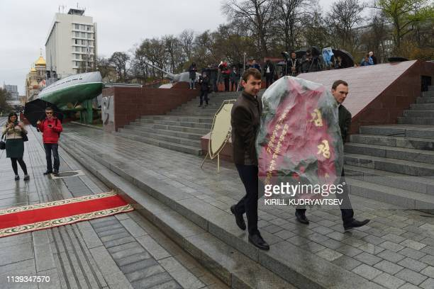 Men carry away a wreath after a wreath-laying ceremony by North Korean leader was cancelled, at a WWII memorial in the far-eastern Russian port of...