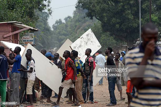 Men carry away items looted in the 5th district of Bangui on February 9 2014 According to witnesses at least ten people have been killed since the...