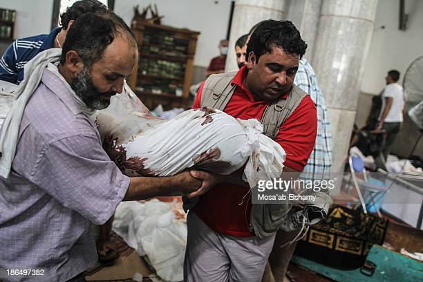 CONTENT] Men carry away the body of a Morsi supporter killed during the violent clearing of Rabaa Adaweya camp
