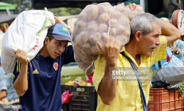 Men carry bags with potatoes in La Parada neighborhood in Cucuta Colombia near the Simon Bolivar International Bridge on the border with Tachira...
