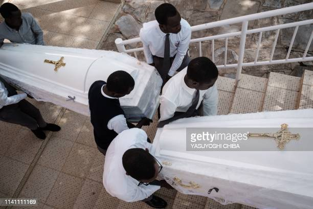 Men carry coffins containing newly discoverd remains of 84,437 victims of the 1994 genocide during a funeral ceremony at the Nyanza Genocide...