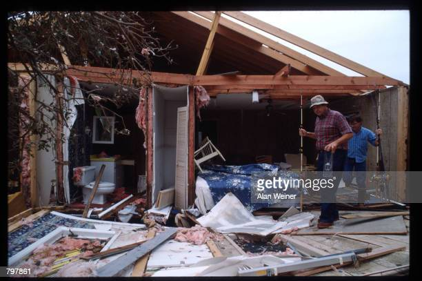 Men carry fishing poles through the remains of a home September 27 1989 in South Carolina Hugo is ranked as the eleventh most intense hurricane to...