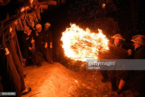 Men carry flaming sticks as they try to set fire to a wooden shrine that is protected by men from Nozawaonsen village during the Nozawaonsen Dosojin...
