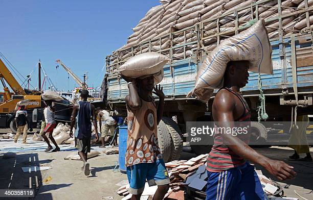 Men carry on November 18 2013 cargo they unloaded from a foreign ship in Bosaso harbor in Puntland After increased security in Somalia's Puntland...