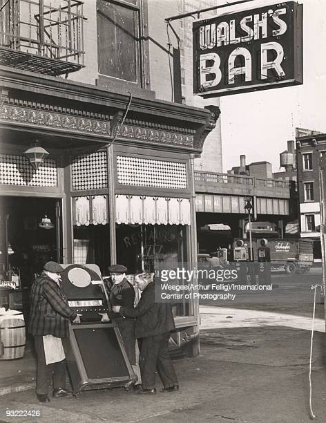 Men carry out a cigarette machine from Walsh's Bar and Grill, located at 213 Tenth Ave. In New York City, after the place was accused of taking bad...