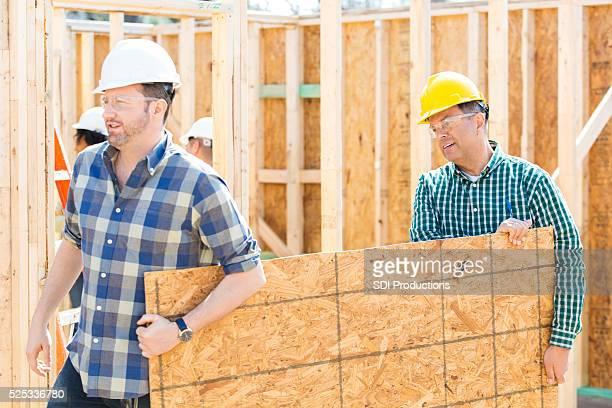 Men carry plywood through construction site