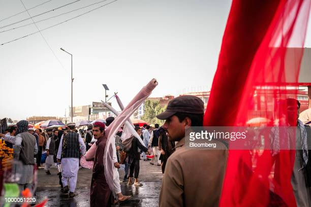Men carry rolls of fabric at a market in Kabul Afghanistan on Thursday July 12 2018 US President Donald last year said 16000 US troops would remain...