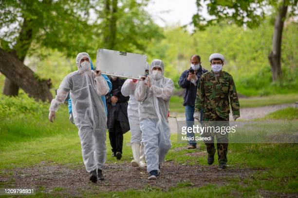 Men carry the body of a COVID-19 victim before burial on April 10, 2020 in Qaem Shahr, Iran. The Coronavirus pandemic has spread to many countries...